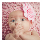 Portrait of a 3-month-old baby girl in a pink headband.