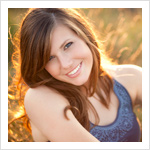 Senior picture of a 2011 senior high schooler in a field with the setting sun behind her.