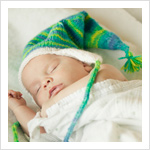 Newborn baby boy sleeping in a white blanket and knit hat.